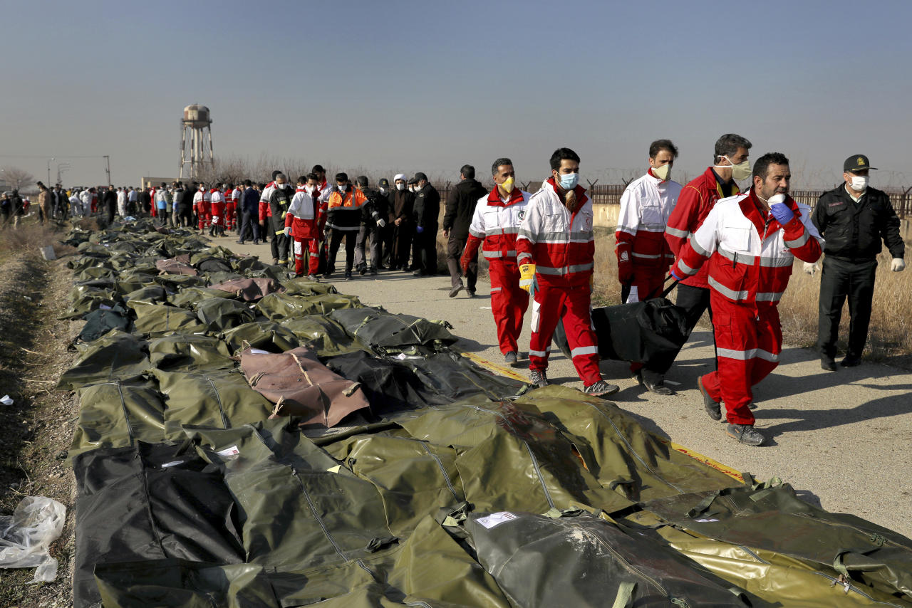 Rescue workers carry the body of a victim of a Ukrainian plane crash in Shahedshahr, southwest of the capital Tehran, Iran, Wednesday, Jan. 8, 2020. A Ukrainian passenger jet carrying 176 people crashed on Wednesday, just minutes after taking off from the Iranian capital's main airport, turning farmland on the outskirts of Tehran into fields of flaming debris and killing all on board. (AP Photo/Ebrahim Noroozi)