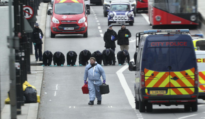 Forensic personnel conduct a fingertip search at the cordoned off area on London Bridge in central London, Sunday. Source: AP