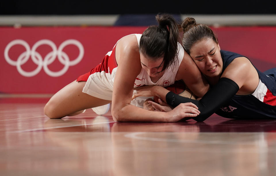 Canada's Bridget Carleton (6), left, and South Korea's Ji Su Park (19) fight for the loose ball during women's basketball preliminary round game at the 2020 Summer Olympics, Thursday, July 29, 2021, in Saitama, Japan. (AP Photo/Charlie Neibergall)