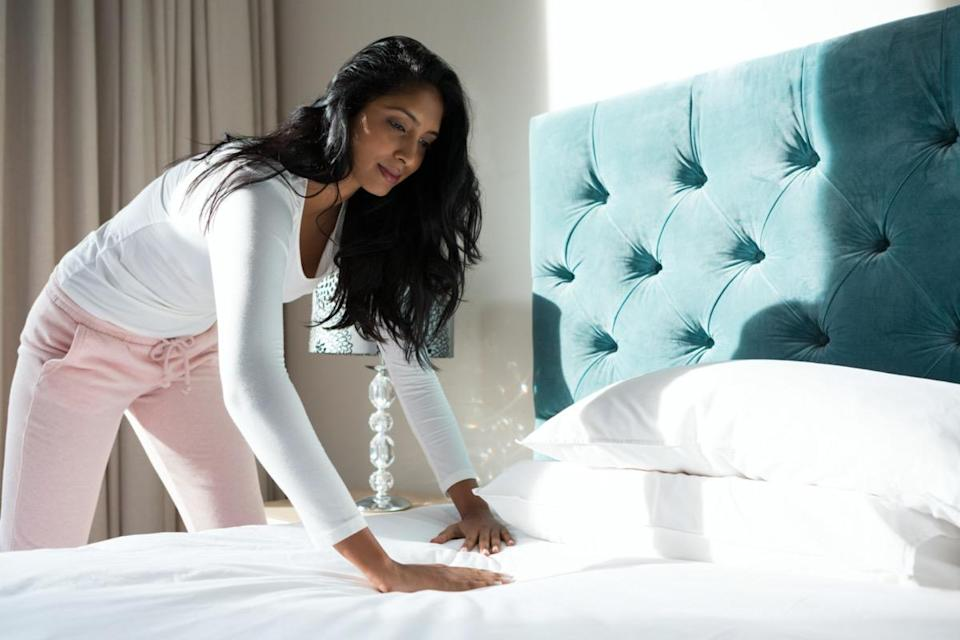 Young woman with long hair making bed at home