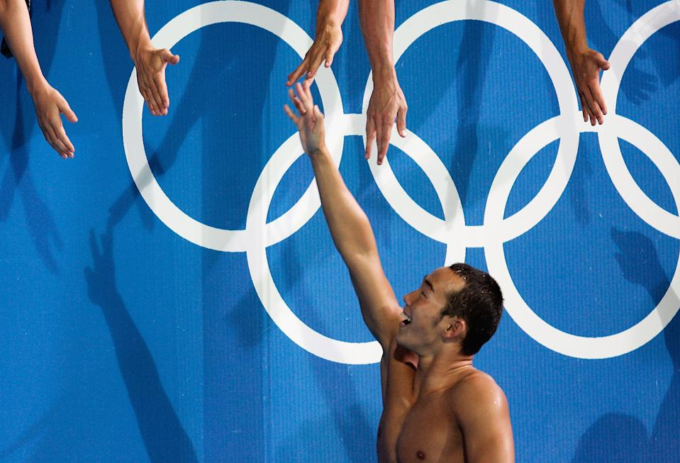 ATHENS - AUGUST 21: Takashi Yamamoto of Japan greets fans after getting the bronze medal for swimming the butterfly leg of the men's swimming 4 x 100 metre medley relay final on August 21, 2004 during the Athens 2004 Summer Olympic Games at the Main Pool of the Olympic Sports Complex Aquatic Centre in Athens, Greece. (Photo by Donald Miralle/Getty Images)