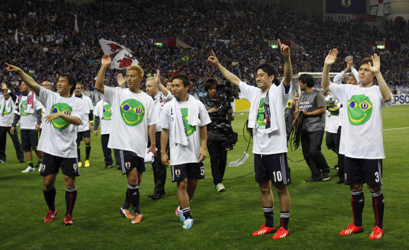Japan's Shinji Kagawa, second right, Keisuke Honda, second left, Yuto Nagatomo, center, with teammates celebrate after their 1-1 draw with Australia during their Asian zone Group B qualifying soccer match for the 2014 World Cup in Saitama, near Tokyo, Tuesday, June 4, 2013. Japan became the first team to reach 2014 World Cup. (AP Photo/Shuji Kajiyama)