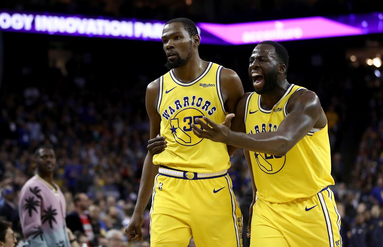 Kevin Durant of the Golden State Warriors is escorted off the court by Draymond Green after Durant was ejected from the game for complaining about a call against the Denver Nuggets at ORACLE Arena in Oakland, California, on April 2, 2019.