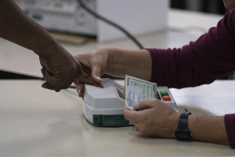 A voter registers her fingerprint before voting at a polling station in the Mare favela in Rio de Janeiro, Brazil, Sunday, Oct. 28, 2018. Jair Bolsonaro, presidential candidate with the Social Liberal Party, is running against leftist candidate Fernando Haddad of the Workers' Party. (AP Photo/Ricardo Borges)