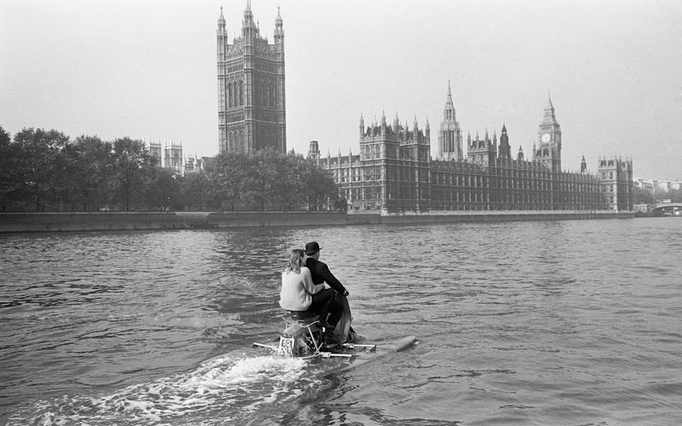 Water scootering back to the office after lunch? It was 'skipper' businessman Jack Hornsby, with his 17 year old daughter Stella sailing pillion, during a try out on the River Thames, London. It is an amphibious motor scooter fitted with two floats which are let down before entering the water. A paddle fixed to the back wheel, and it is steered by a rudder controlled by the handlebars 20th October 1965 U9429 . (Photo by George Greenwell/Mirrorpix/Getty Images) - Getty