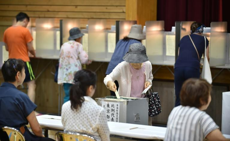 Voters cast their ballots at a polling station in Tokyo