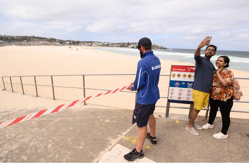 A ranger tapes off an entrance to Bondi Beach following its closure to the public. Source: AAP