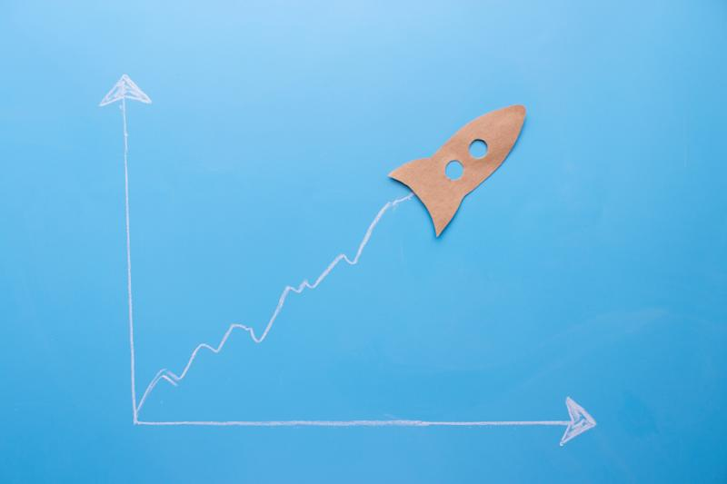 A brown paper cut out of a rocket appearing to soar on a chart drawn on a blue piece of paper.
