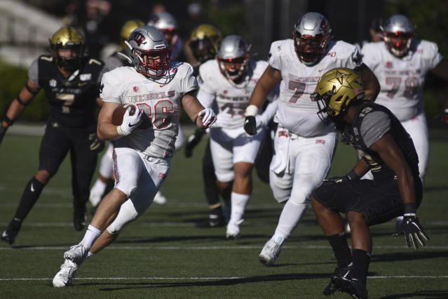 UNLV running back Chad Maygar (38) runs next to Vanderbilt defender Brendon Harris (13) in the first half of an NCAA college football game Saturday, Oct. 12, 2019, in Nashville, Tenn. (AP Photo/Mike Strasinger)