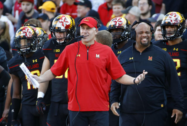 In this Oct. 14, 2017, file photo, Maryland head coach DJ Durkin, center, stands on the sideline in the first half of an NCAA college football game against Northwestern in College Park, Md. The Atlanta Falcons have brought in former Maryland coach DJ Durkin to serve as a guest coach during training camp, drawing immediate scrutiny over the wisdom of taking on someone who was fired from his previous job after a player's death. This is the first coaching stint for Durkin since he was dismissed by the Terrapins last October. (AP Photo/Patrick Semansky, File)