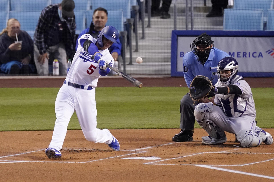 Los Angeles Dodgers' Corey Seager, left, hits a solo home run as Colorado Rockies catcher Elias Diaz, right, watches along with home plate umpire Tom Hallion during the first inning of a baseball game Tuesday, April 13, 2021, in Los Angeles. (AP Photo/Mark J. Terrill)