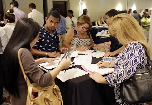 People filling out job applications at a job fair, in Miami Lakes, Fla. (AP Photo/Lynne Sladky, File)
