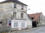 """The run-down cafe """"Au Paradis"""" (in Heaven""""), its sign and paintwork faded over time. (Reuters)"""