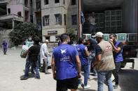 Members of the al-Ghina NGO distribute boxes of food for people in need, near the scene of last week's explosion, in Beirut, Lebanon, Tuesday, Aug. 11, 2020. In the absence of the state, acts of kindness and solidarity have been numerous and striking. Many extended a helping hand far beyond their circle of friends or family, taking to social media to spread the word that they have a room to host people free of charge. And on the streets, it was young volunteers with brooms, not government workers, who swept the streets littered with shattered glass. (AP Photo/Hussein Malla)