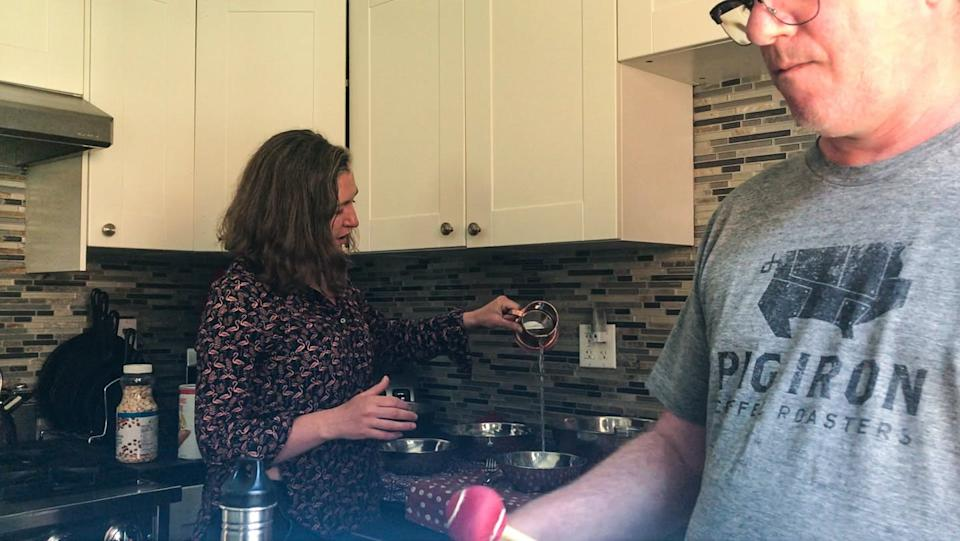 A couple in a kitchen makes music with kitchen objects.