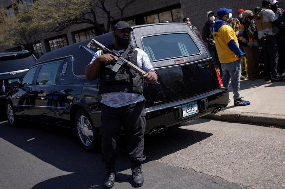A member of the Minnesota Freedom Fighters militia guards the car carrying Duante Wright's coffin