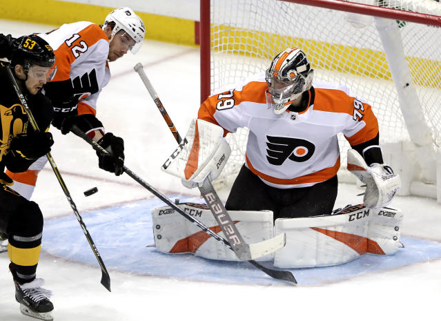 Pittsburgh Penguins' Teddy Blueger (53) can't get his stick on a rebound in front of Philadelphia Flyers goaltender Carter Hart (79) with Michael Raffl (12) defending during the first period of an NHL hockey game in Pittsburgh, Sunday, March 17, 2019. (AP Photo/Gene J. Puskar)