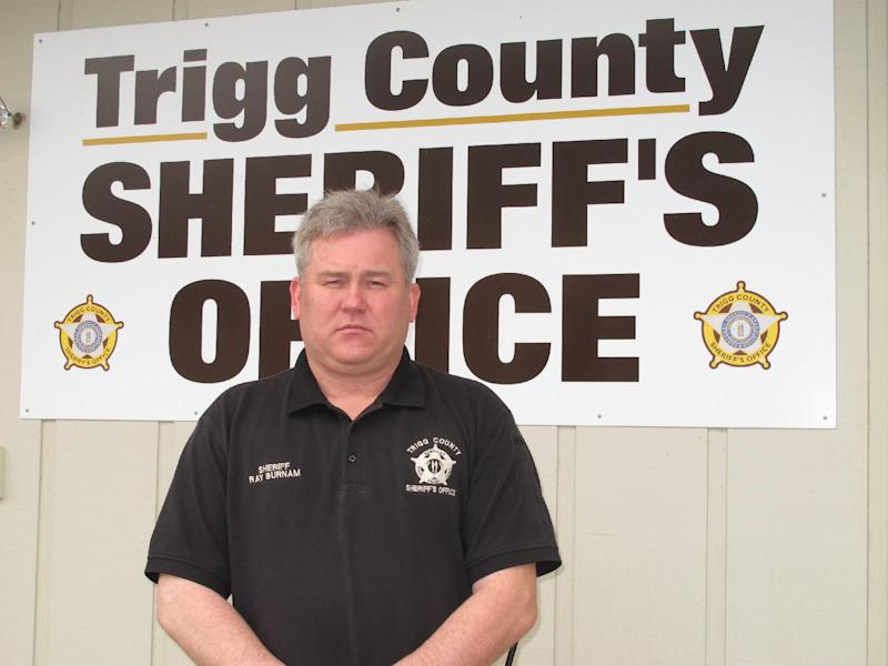 "In  this Tuesday, Dec. 4, 2012, photo, Trigg County Sheriff Ray Burnam stands in front of the sheriff's department in Cadiz, Ky. When Burnam offered $1,000 of his own money as a reward for information leading to a conviction in three unsolved murder cases in western Kentucky county, law enforcement issued a court order demanding Burnam turn over his findings in one case and claimed he had gone ""rogue"". AP Photo/Bruce Schreine"