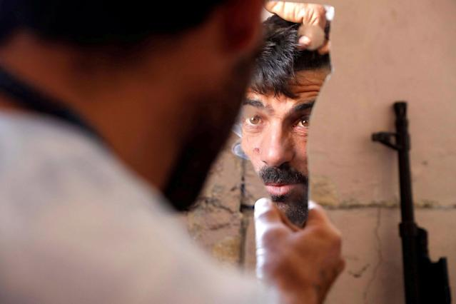 <p>A fighter of Syrian Democratic Forces fixes his hair using a broken mirror at the frontline in Raqqa, Syria, Oct. 6, 2017. (Photo: Erik De Castro/Reuters) </p>