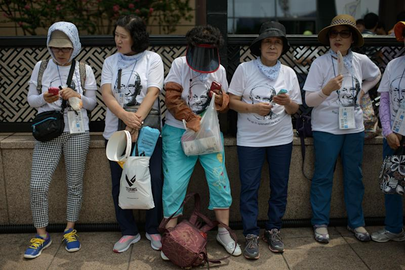 Catholic worshippers wearing papal T-shirts gather for a mass lead by Pope Francis, at Gwanghwamun Square in central Seoul, South Korea, on August 16, 2014 (AFP Photo/Ed Jones)