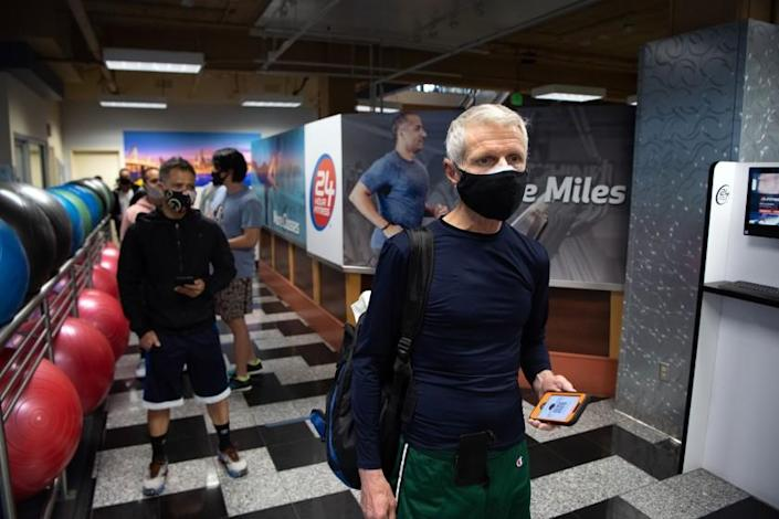 SAN FRANCISCO, CA - MARCH 03, 2021 - Reese Bacon (R) waits in line to check in for his reservation to work out at a 24 Hour Fitness gym in San Francisco, California on March 03, 2021. As San Francisco moves into the red tier of the Covid-19 pandemic, gyms are now allowed to open at a maximum 10% capacity. (Josh Edelson/for the Times)