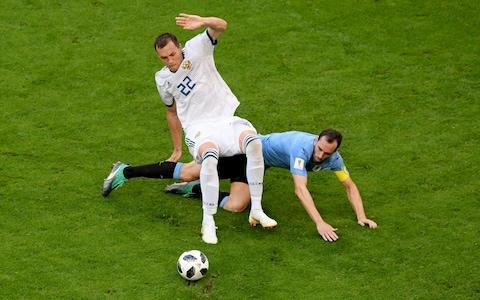 Diego Godin of Uruguay tackles Artem Dzyuba of Russia during the 2018 FIFA World Cup Russia group A match between Uruguay and Russia at Samara Arena on June 25, 2018 in Samara, Russia - Credit: Getty Images