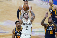 New Orleans Pelicans guard Lonzo Ball (2) goes to the basket between Utah Jazz guard Donovan Mitchell (45) and guard Jordan Clarkson (00) in the first half of an NBA basketball game in New Orleans, Monday, March 1, 2021. (AP Photo/Gerald Herbert)