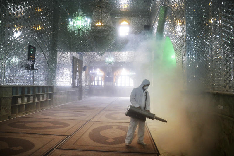 FILE - In this March, 6, 2020, file photo, a firefighter disinfects the shrine of Saint Saleh to help prevent the spread of the new coronavirus in northern Tehran, Iran. As cases of the coronavirus surge in Italy, Iran, South Korea, the U.S. and elsewhere, many scientists say it's plain that the world is in the grips of a pandemic — a serious global outbreak. (AP Photo/Ebrahim Noroozi, File)