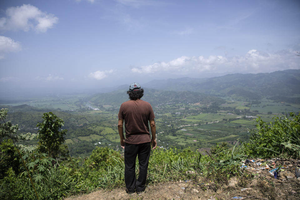 """Friar Leopoldo Serrano surveys the landscape where he built a rehab center for drug addicts, in Mission San Francisco de Asis, Honduras, Tuesday, July 15, 2021. As Serrano stood on the lookout over the valley, he said, """"Half of all the land and businesses you see from here belong to drug traffickers."""" (AP Photo/Rodrigo Abd)"""