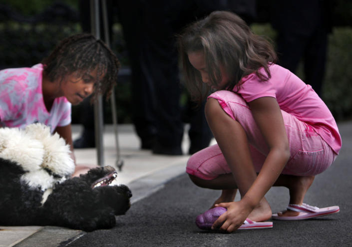 FILE - In this Sept. 15, 2009, file photo Malia Obama, left, and Sasha Obama play with family dog Bo as they wait for President Barack Obama to arrive on the South Lawn of the White House in Washington. Former President Barack Obama's dog, Bo, died Saturday, May 8, 2021, after a battle with cancer, the Obamas said on social media. (AP Photo/Gerald Herbert)