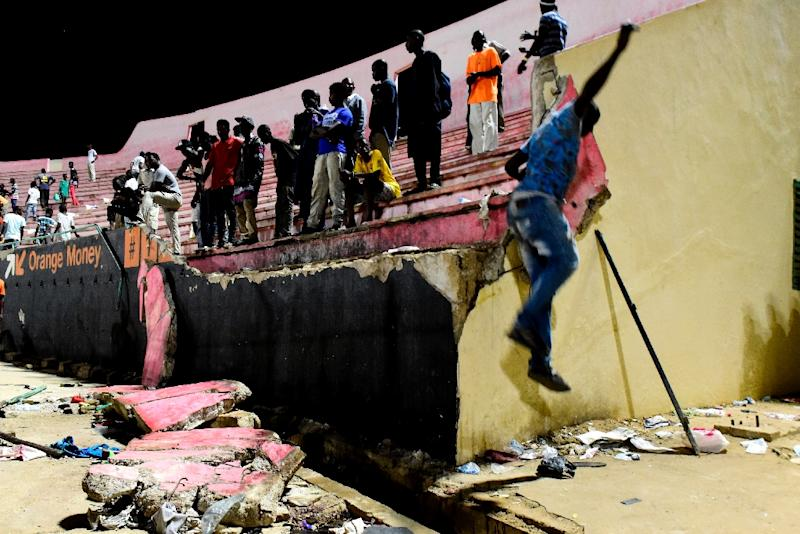 A wall collapsed onto fans fleeing the stadium to escape the hail of projectiles, with some crushed in the panic Eight people died and dozens more were injured in the crush (AFP Photo/SEYLLOU)