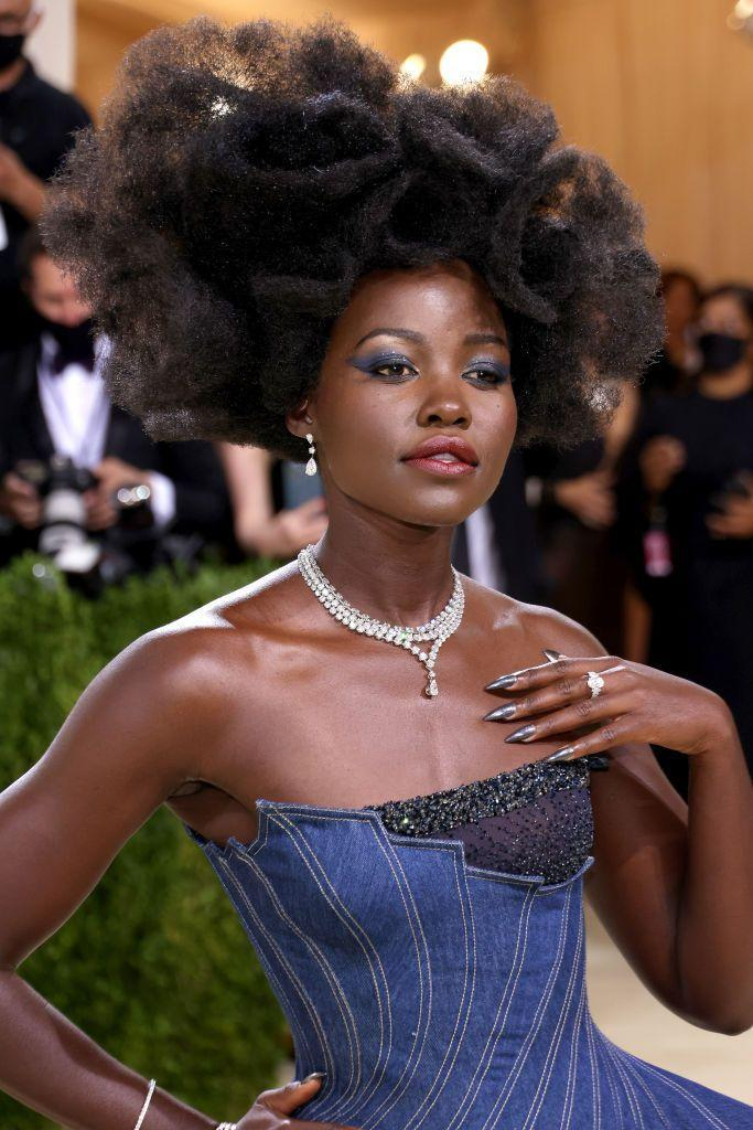 <p>Lupita Nyong'o punctuated her full denim look with an asymmetrical afro strategically placed so it doesn't overshadow her sharp navy blue winged eyeshadow. </p>