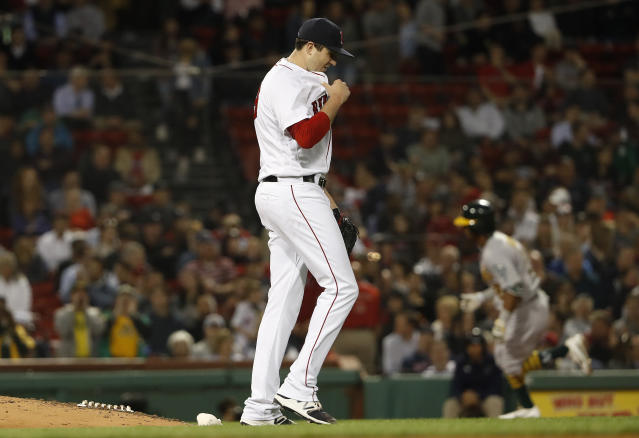 Boston Red Sox relief pitcher Carson Smith walks off the mound as Oakland Athletics' Khris Davis rounds the bases after his home run during the eighth inning of a baseball game at Fenway Park in Boston Monday, May 14, 2018. (AP Photo/Winslow Townson)