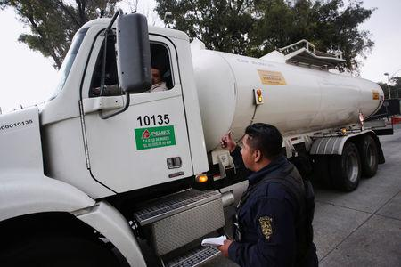 A police officer talks to the driver of a fuel truck as it leaves a distribution center in Mexico City, Mexico January 12, 2019. REUTERS/Daniel Becerril