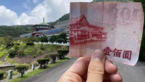 The Reddit user, nicknamed @IB-45, holds a half-folded NT$100 Taiwanese bill, which perfectly aligns with the building in the background, leading many to question whether the picture is real. (Courtesy of @IB-45/Reddit)