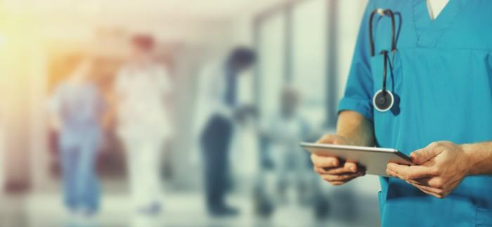 A person in hospital scrubs looking at a tablet in a hospital hallway.