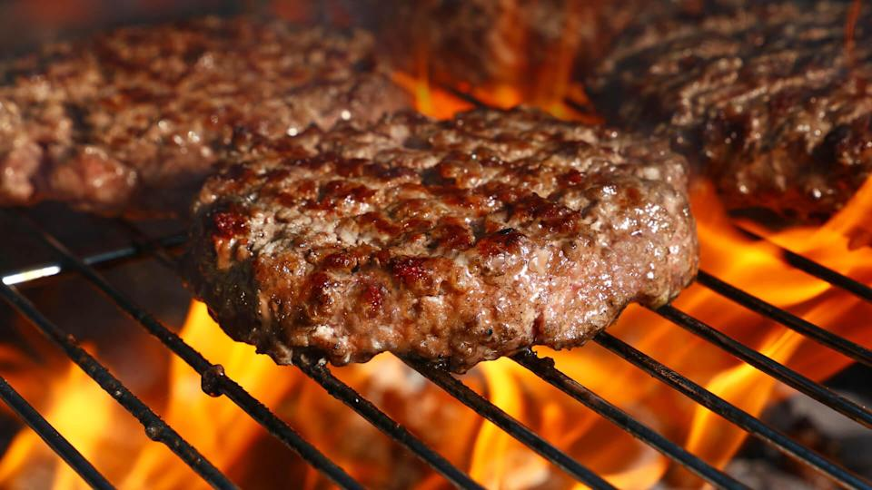 Close up beef or pork meat barbecue burgers for hamburger prepared grilled on bbq fire flame grill, high angle view.