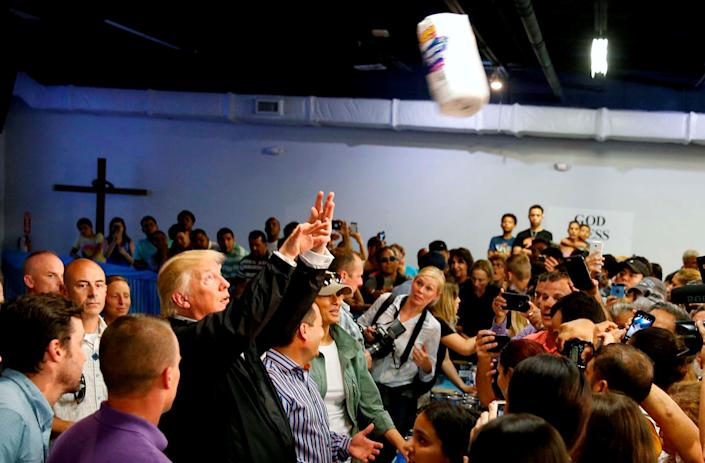 Trump throws rolls of paper towels into a crowd of Puerto Rico residents affected by Hurricane Maria as he visits Calgary Chapel in San Juan on Oct. 3.