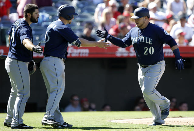 Seattle Mariners designated hitter Daniel Vogelbach, right, gets congratulations from Kyle Seager, center, and David Freitas after hitting a two-RBI home run during the fourth inning of a baseball game against the Los Angeles Angels in Anaheim, Calif., Sunday, Sept. 16, 2018. (AP Photo/Alex Gallardo)