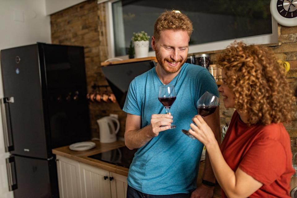 Happy young girlfriend and boyfriend drinking wine at the kitchen in the evening.