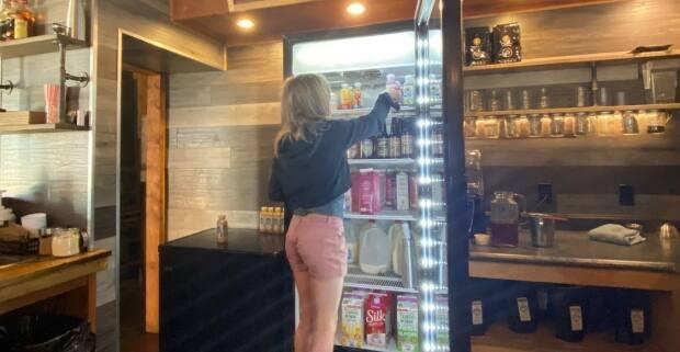 Cafe owner Chris Fawbert's daughter helps stock the beverage cooler at the family's Campbell River cafe.  (Chris Fawbert/Facebook - image credit)