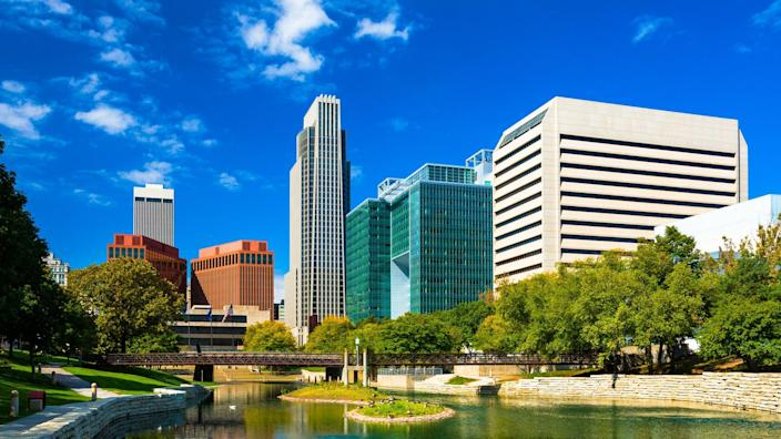 Downtown Omaha skyline with the Gene Leahy Mall in the foreground (including a reflective waterway / lagoon.