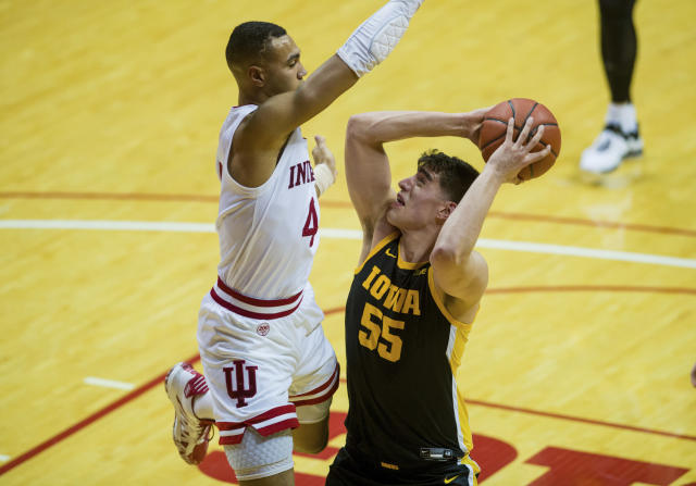 Iowa center Luka Garza (55) works to get a shot away as he is defended by Indiana forward Trayce Jackson-Davis (4) during the second half of an NCAA college basketball game, Thursday, Feb. 13, 2020, in Bloomington, Ind. (AP Photo/Doug McSchooler)