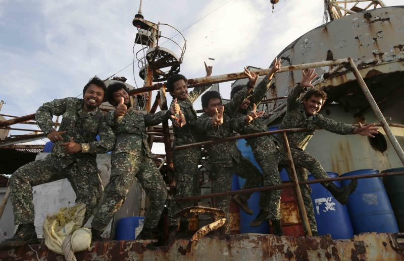 Philippine Marines, who were deployed for almost five months now, pose for a local television news crew aboard the Philippine Navy ship LT 57 Sierra Madre off Second Thomas Shoal (local name Ayungin Shoal) Saturday, March 29, 2014 off South China Sea. China Coast Guard vessel attempted to block the vessel earlier which carried supplies and troops to replace their fellow marines who were deployed for almost five months.(AP Photo/Bullit Marquez)