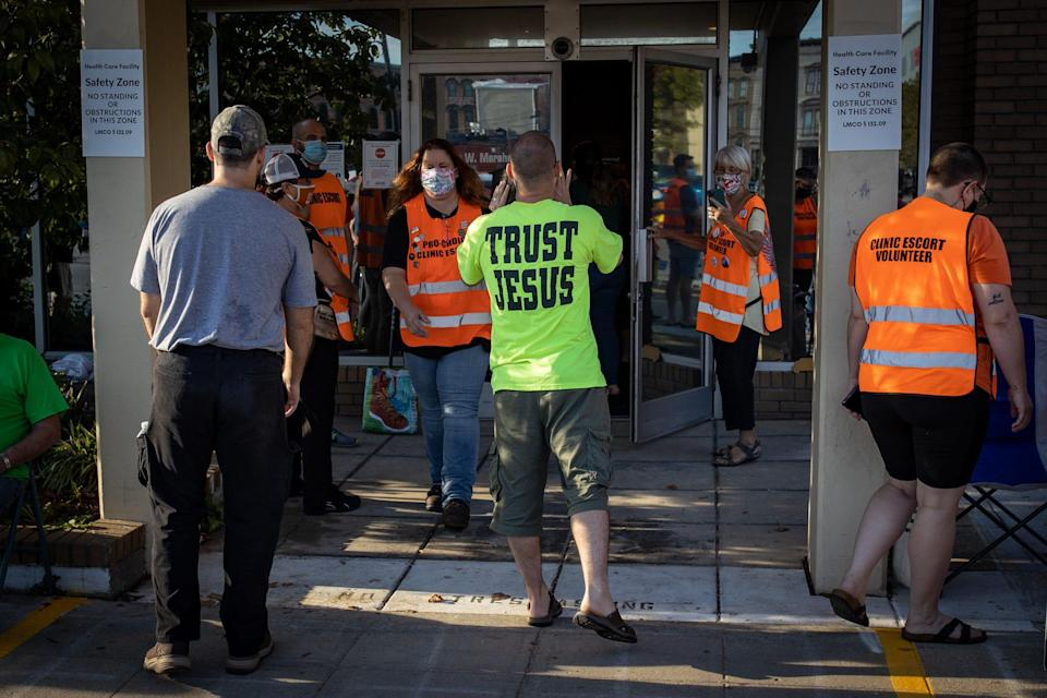 Anti-abortion protesters walk into the restricted safety zone space outside the EMW Women's Surgical Center facility on West Market Street on Saturday morning as they antagonize anyone entering the building Saturday morning. Sept. 18, 2021