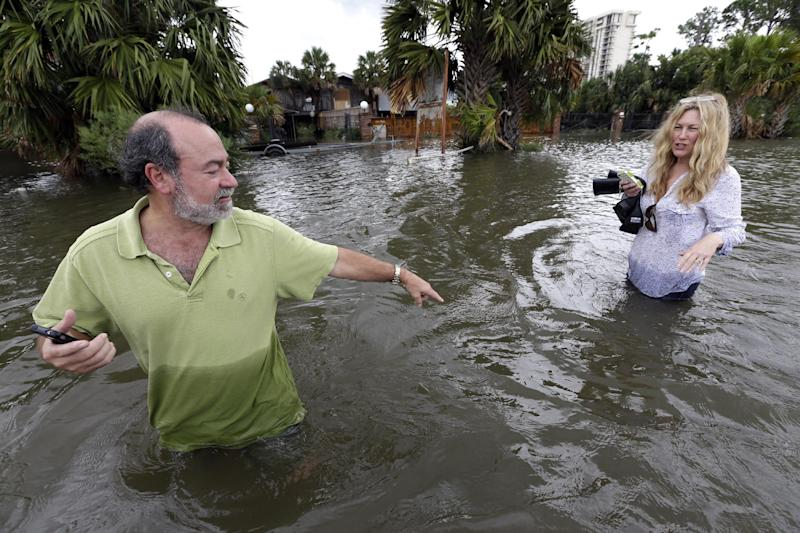 Kenny Melkin, left, helps his wife Becky navigate through floodwaters from Hurricane Isaac as they make their way to see their flooded home in the West End Park neighborhood along Lake Pontchartrain, Friday, Aug. 31, 2012 in New Orleans. Isaac is now a tropical depression and the center was on track to cross Arkansas on Friday and southern Missouri on Friday night, spreading rain as it goes. (AP Photo/David J. Phillip)