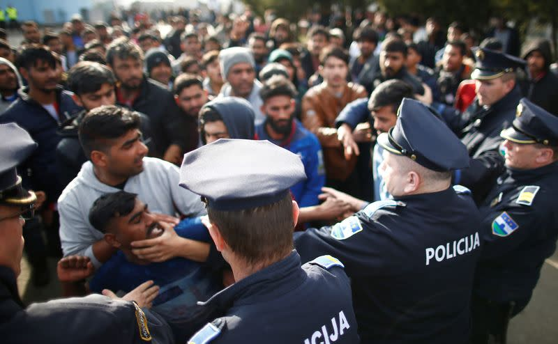 Migrants scuffle with police as they try to block a road in front of the refugee camp Miral in Velika Kladusa