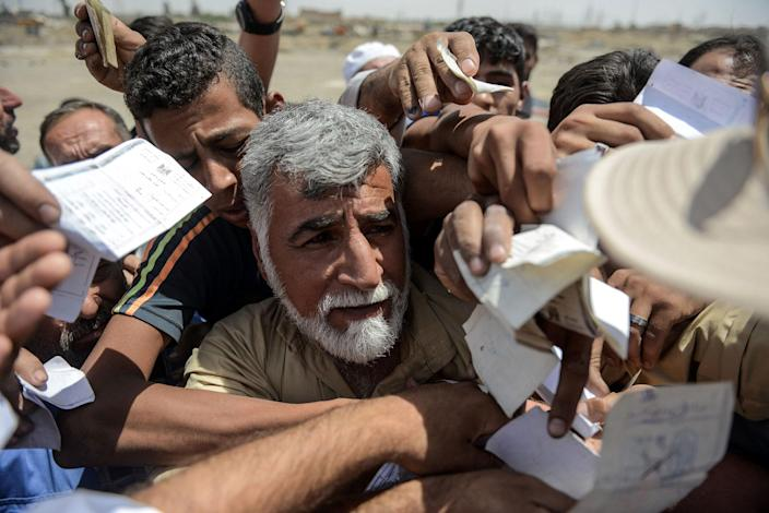 <p>Iraqis queue to receive food rations in an area outside Mosul's Old City on June 22, 2017, during the ongoing offensive by Iraqi forces to retake the last district still held by the Islamic State (IS) group. (Photo: Mohamed el-Shahed/AFP/Getty Images) </p>