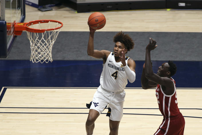 West Virginia guard Miles McBride (4) drives to the basket past Oklahoma forward Kur Kuath (52) during the first half of an NCAA college basketball game Saturday, Feb. 13, 2021, in Morgantown, W.Va. (AP Photo/Kathleen Batten)