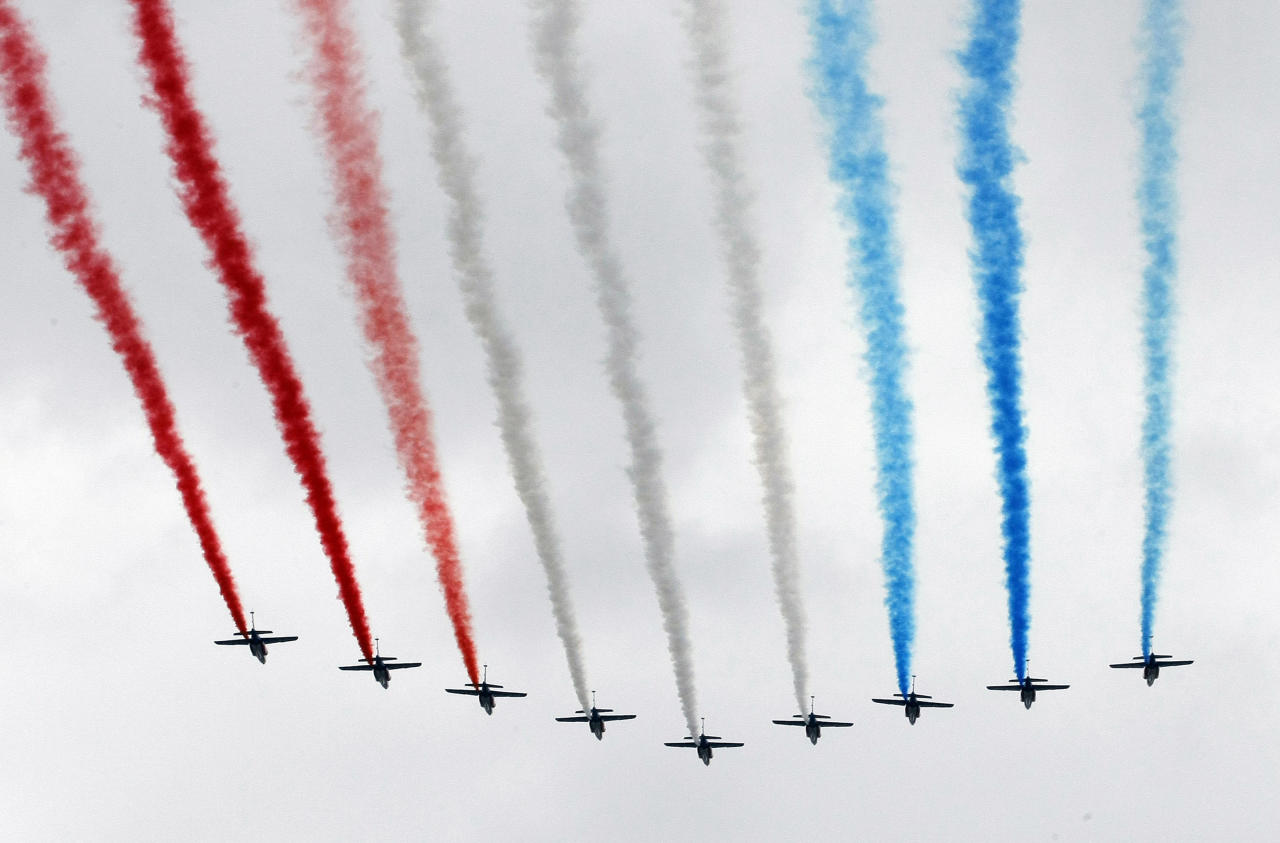 The Patrouille de France aerobatic team fly over the Champs Elysees avenue to open the Bastille Day military parade, Paris, Saturday, July 14, 2012. (AP Photo/Jacques Brinon, Pool)